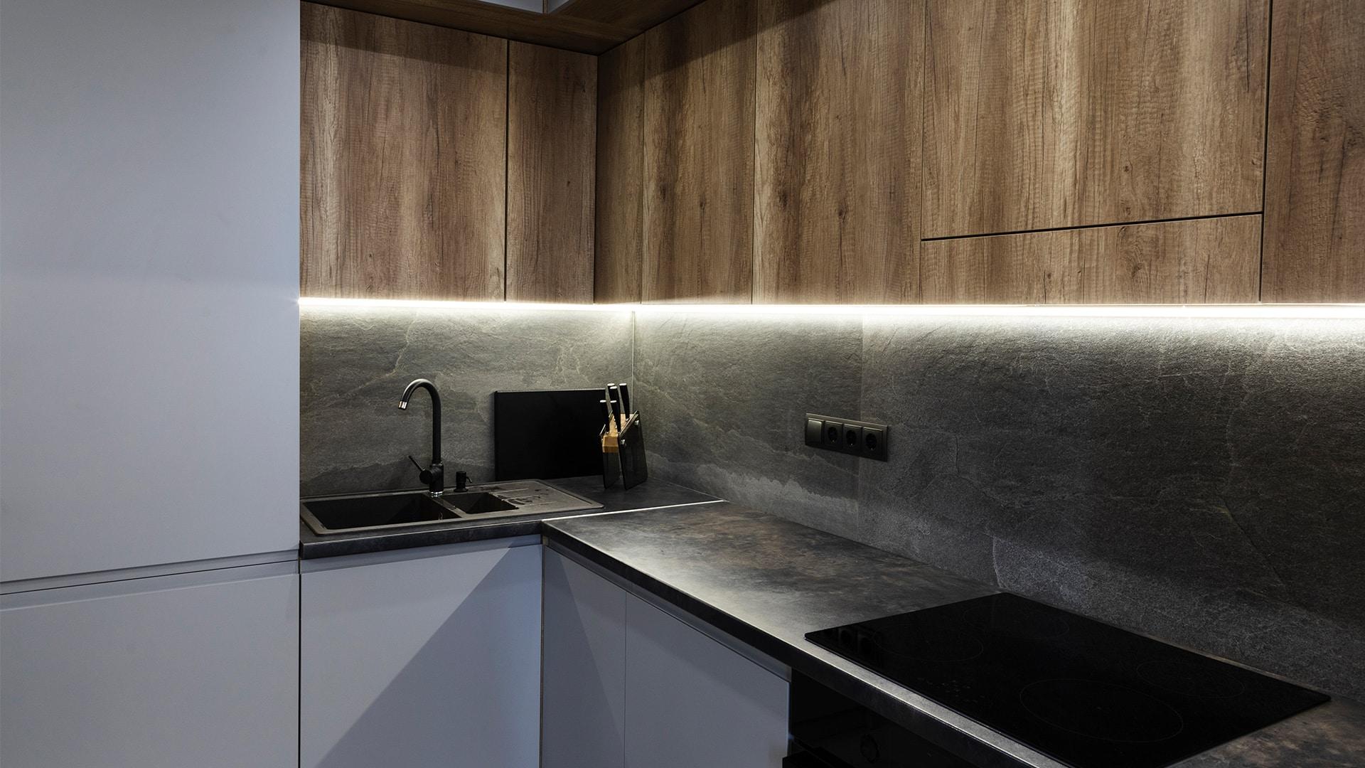 Stylowa kuchnia na wymiar z oświetleniem LED blatu oraz płytą zablatową