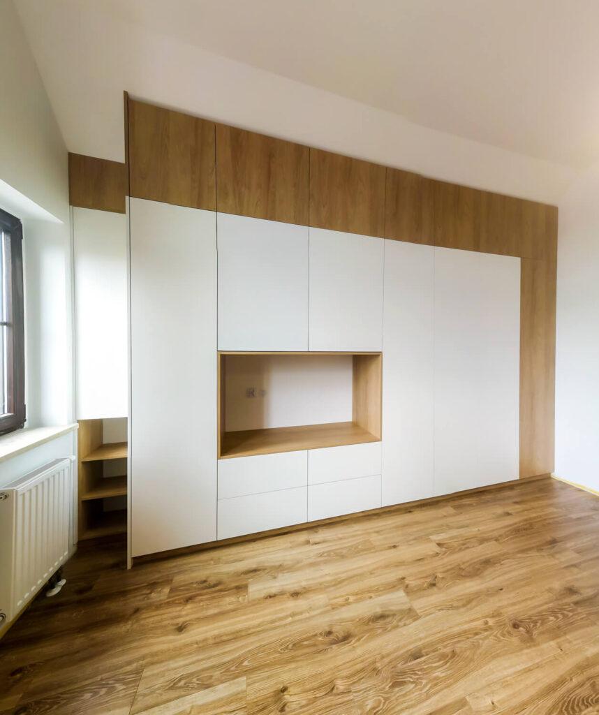 Biała szafa z miejscem na TV i wstawkami drewnianymi na szerokość pokoju