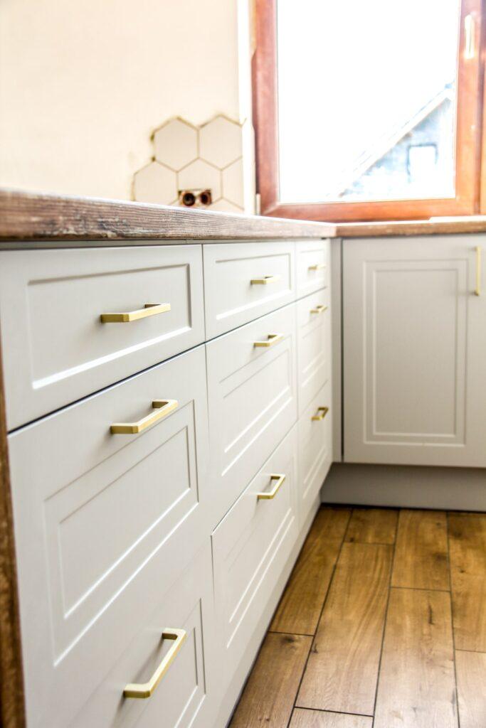 Fronty frezowane ze złotymi uchwytami w białej nowoczesnej kuchni