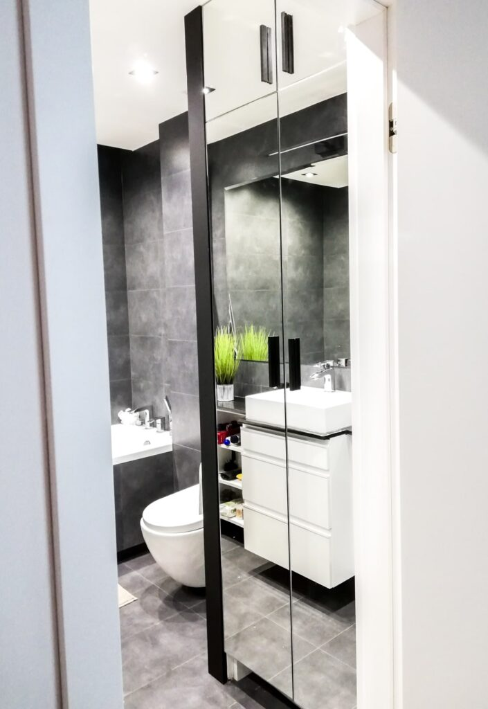 Szafa w łazience ze szklanymi drzwiami oraz uchwytami