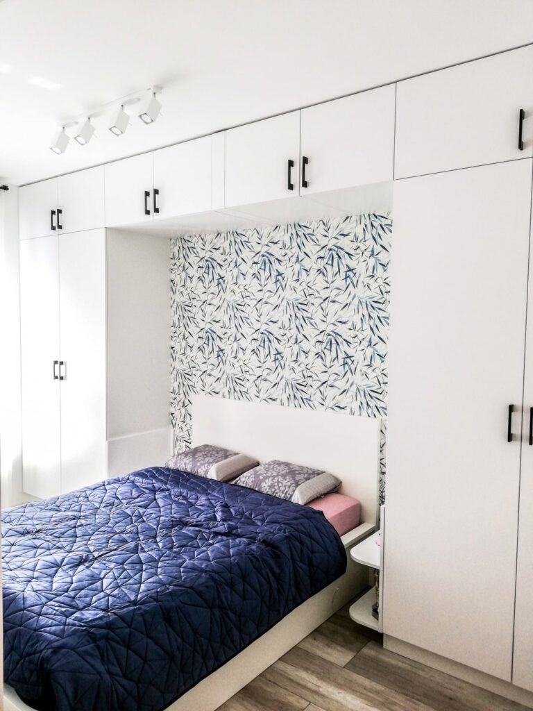 Zabudowa nad łóżkiem w sypialni z szafami po bokach