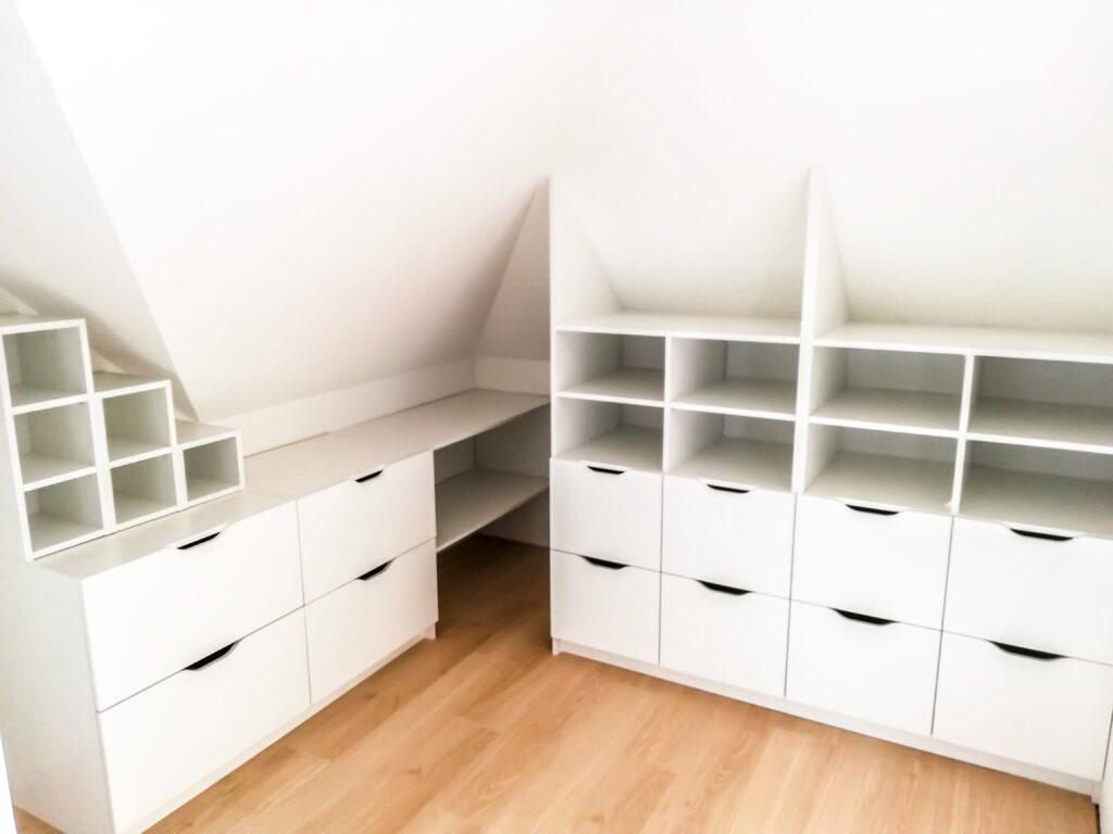 Zabudowa skosu białymi regałami z szufladami oraz półkami