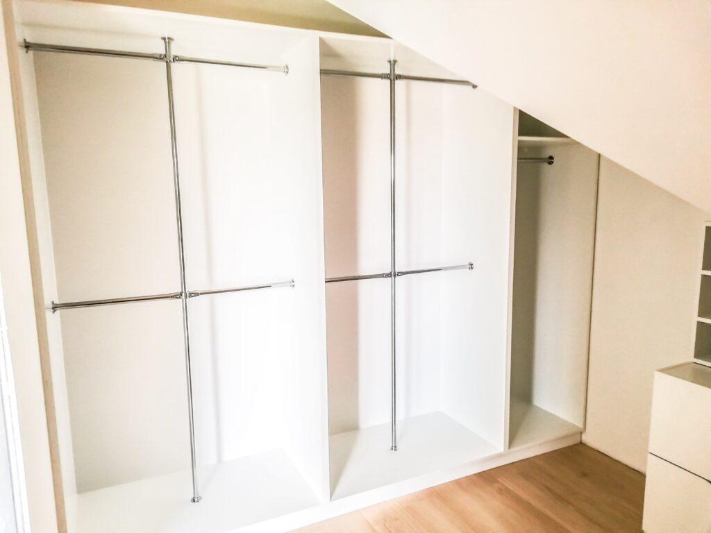 Otwarta biała zabudowa w garderobie z miejscami na wieszaki