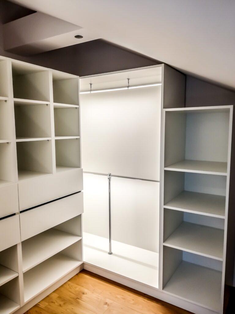 Otwartia biała garderoba na poddaszu z podświetleniem LED