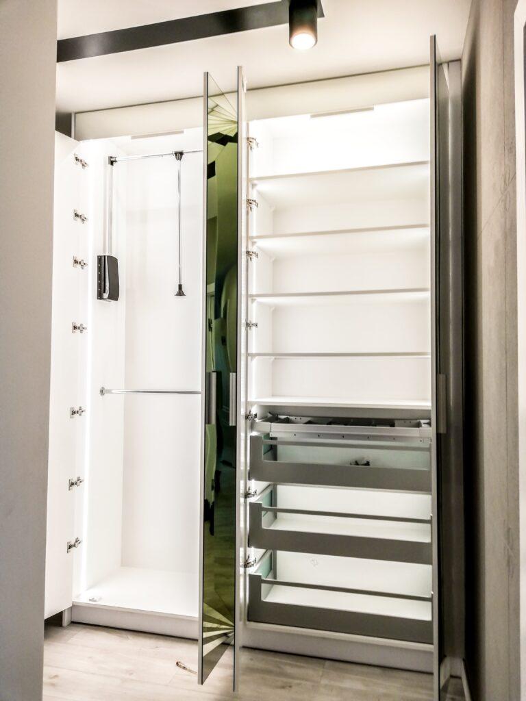 Otwarta szafa z przeszklonymi drzwiami w kolorze zielonym oraz wewnętrznym podświetleniem LED