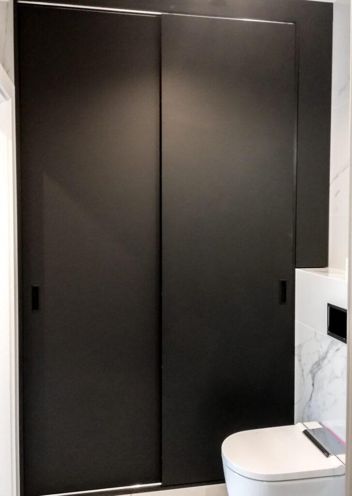 Czarna zabudowa w łazience z półkami koło toalety