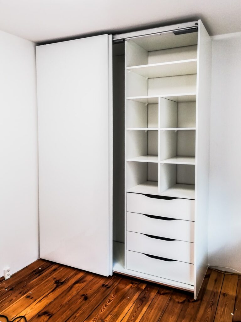 Otwarta biała szafa z szufladami wewnętrznymi