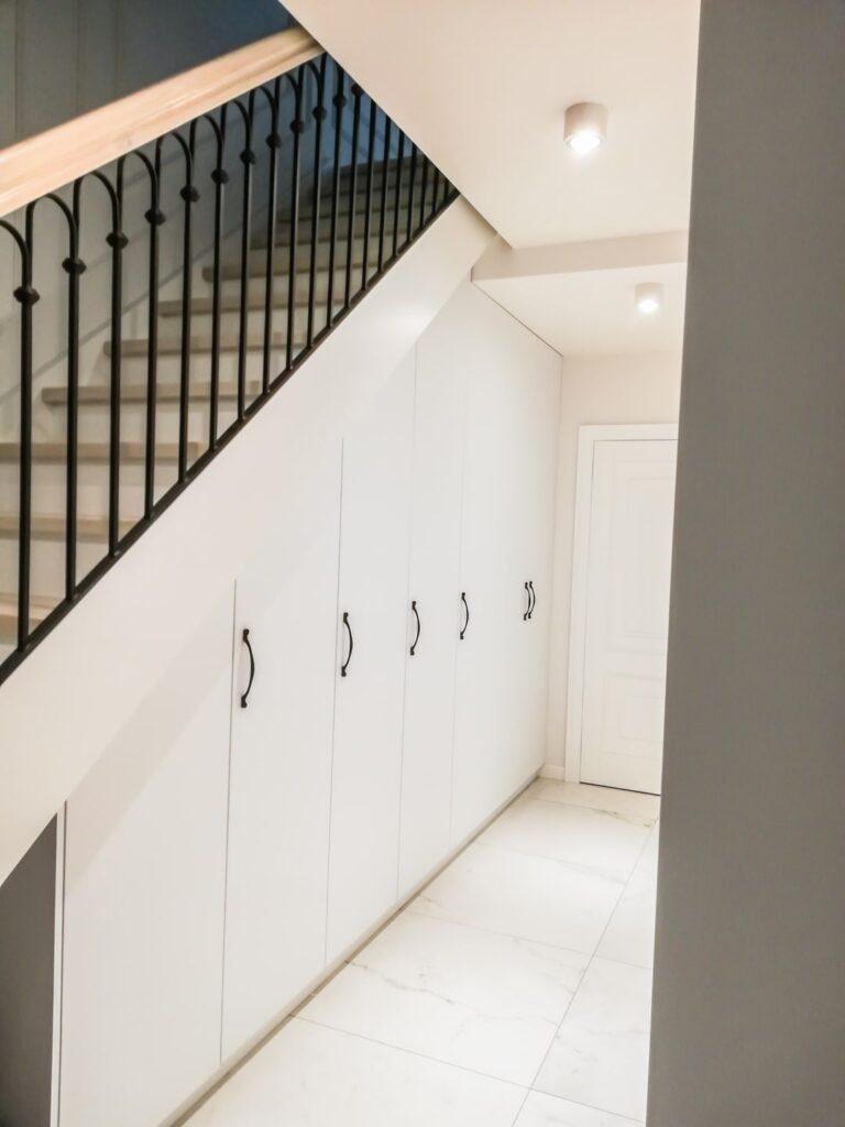 Biała szafa wnękowa pod schodami ze skosem
