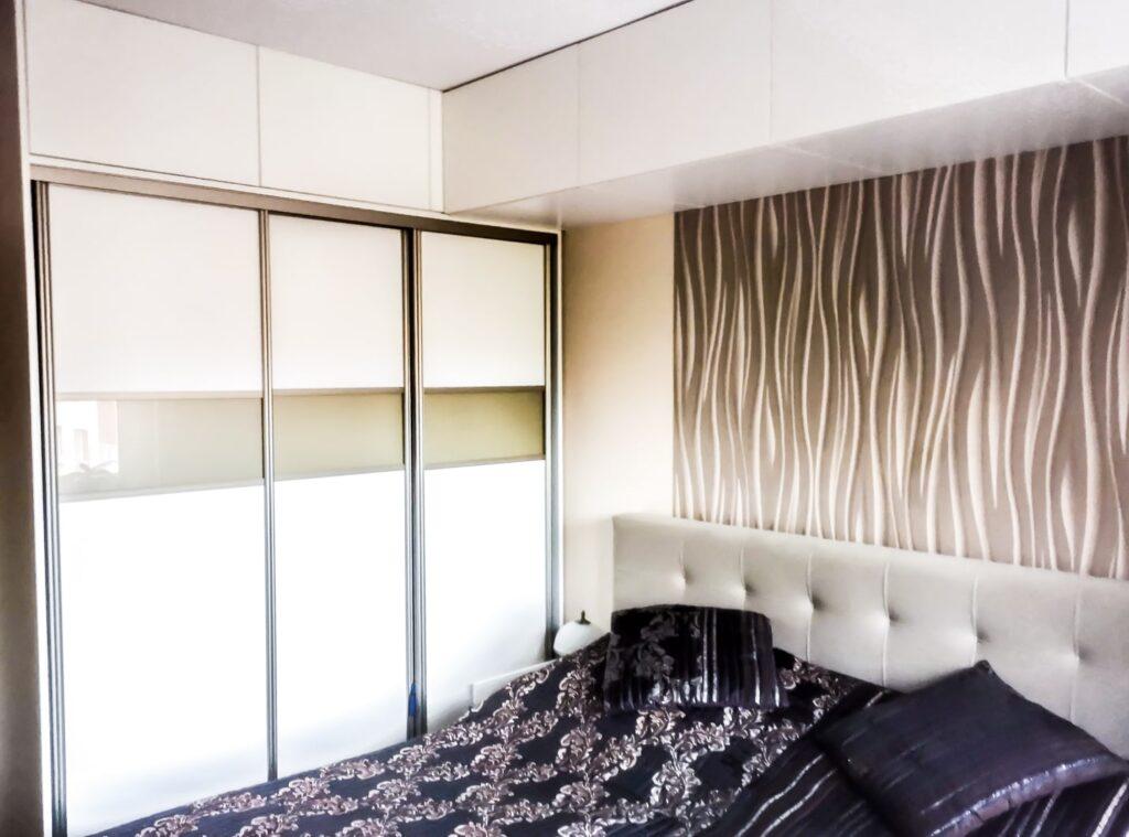 Biała szafa przesuwna ze złotymi wstawkami w sypialni