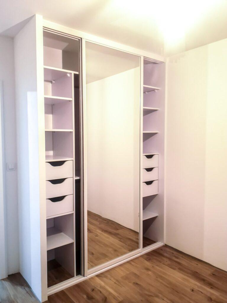 Otwarta biała szafa z drzwiami lustrzanymi oraz szufladami wewnętrznymi