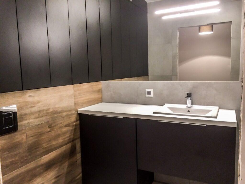 Ciemna zabudowa z szafkami w łazience