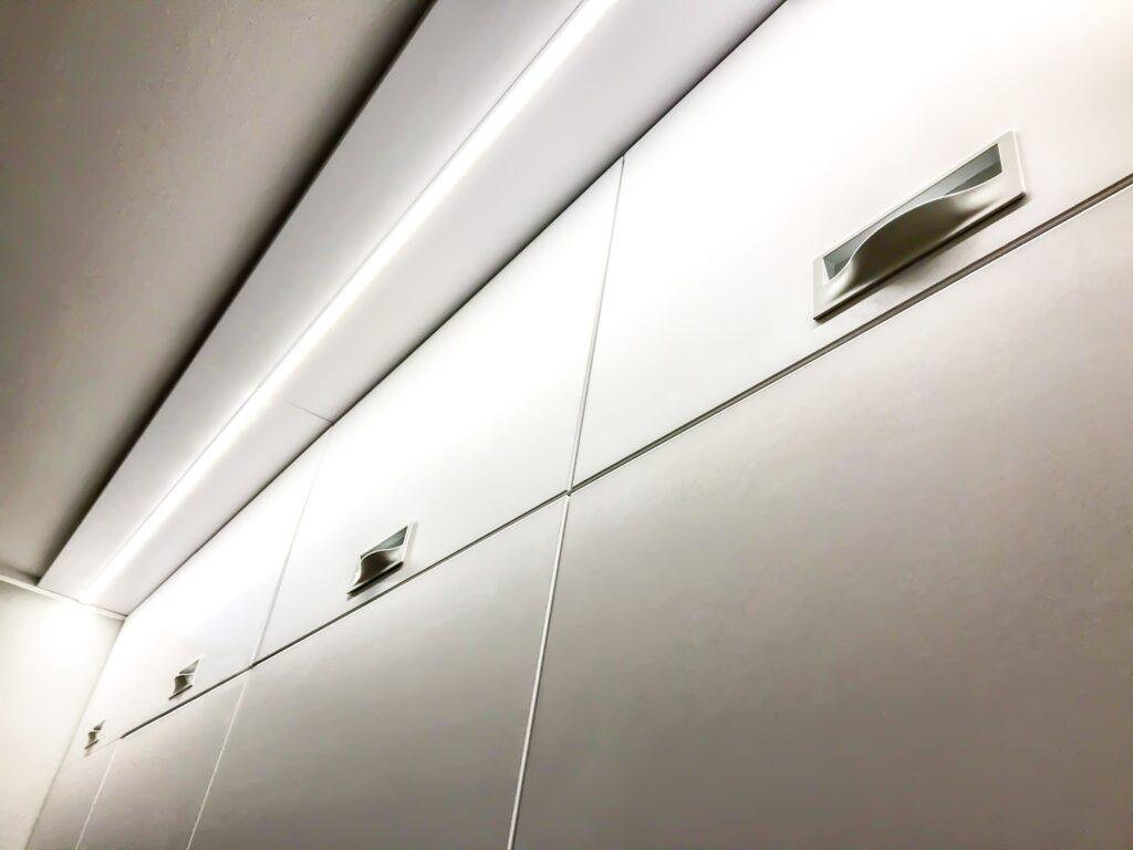 Podświetlenie LED białej szafy z uchwytami wpuszczanymi