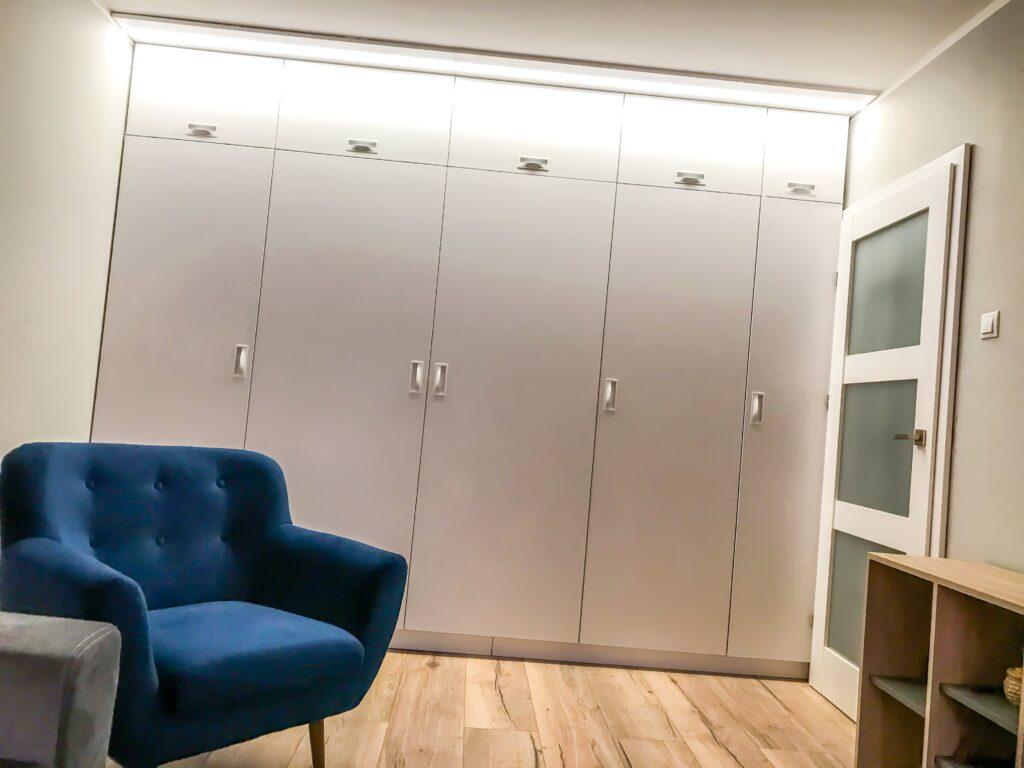 Szafa z podświetleniem LED oraz uchwytami wpuszczanymi na szerokość pokoju