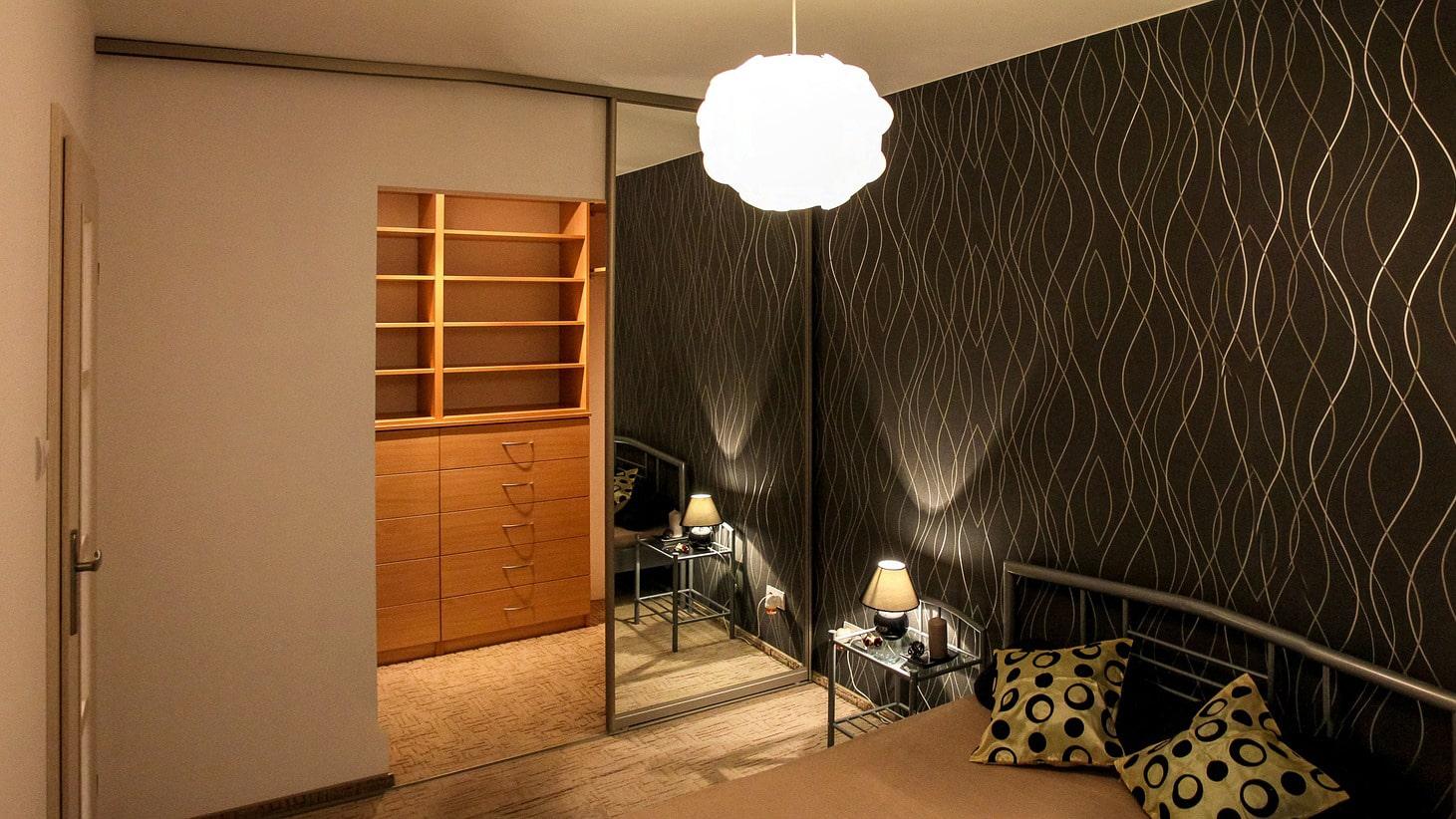 szafa z lustrem i drzwiami do garderoby w sypialni