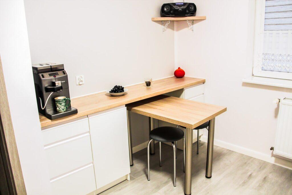 Drewnopodobny blat z podsuwanym stolikiem w białej kuchni