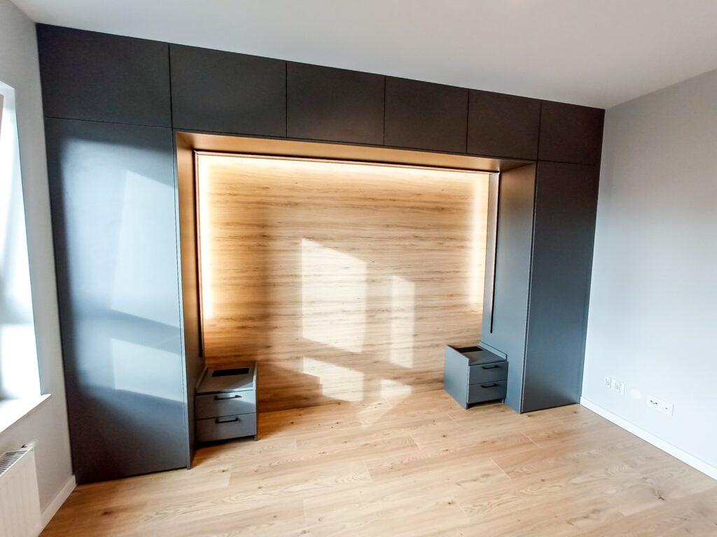 Czarna matowa zabudowa nad łóżkiem z szafkami nocnymi i podświetleniem LED