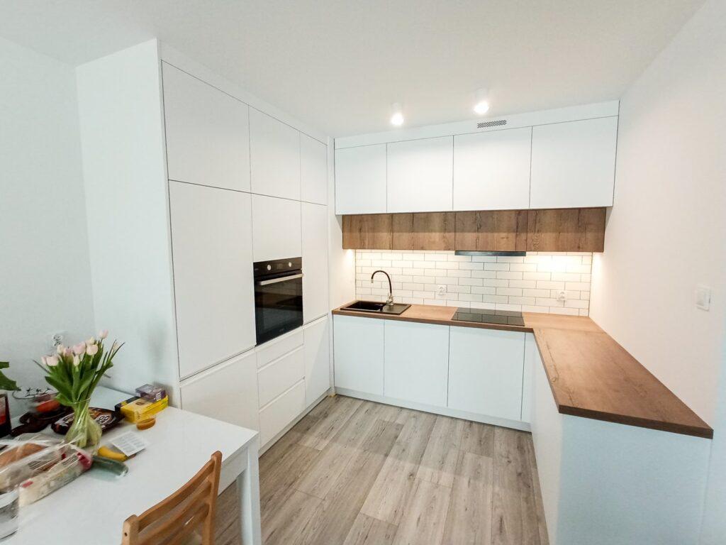 Prosta i nowoczesna biało-drewniana kuchnia ze słupkiem i lodówką w zabudowie