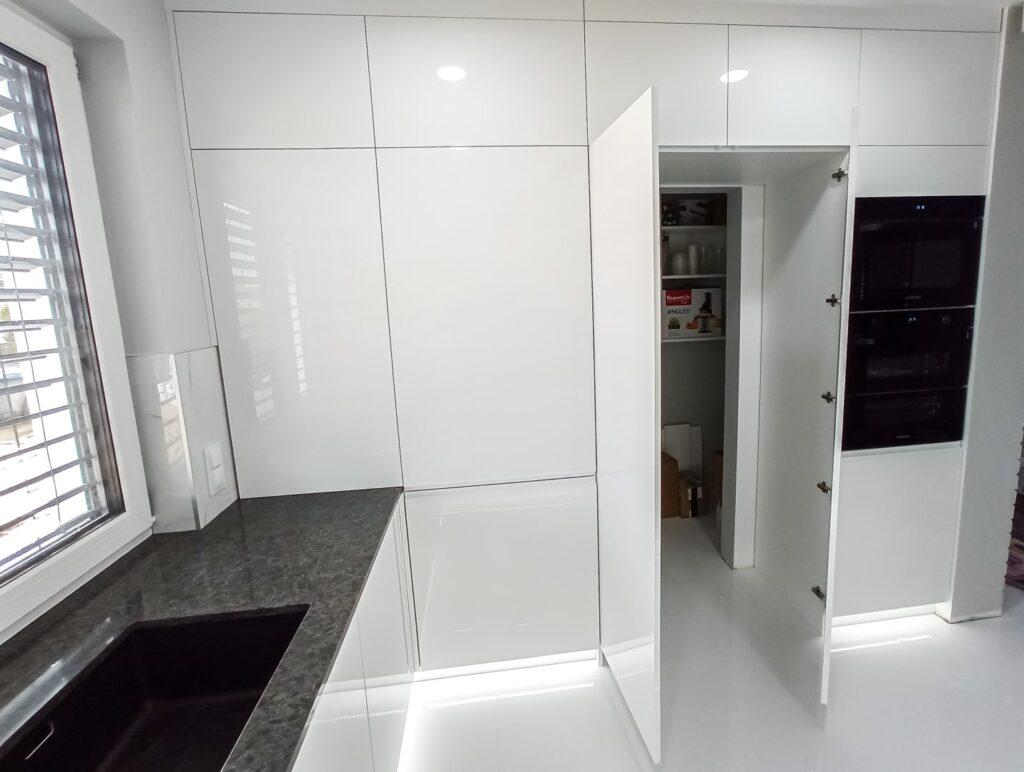 Otwarte przejście do spiżarki w białej kuchni