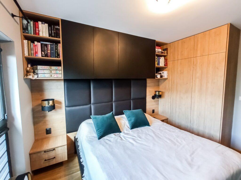 Czarna zabudowa za łóżkiem z panelem tapicerowanym i drewnianymi szafkami nocnymi