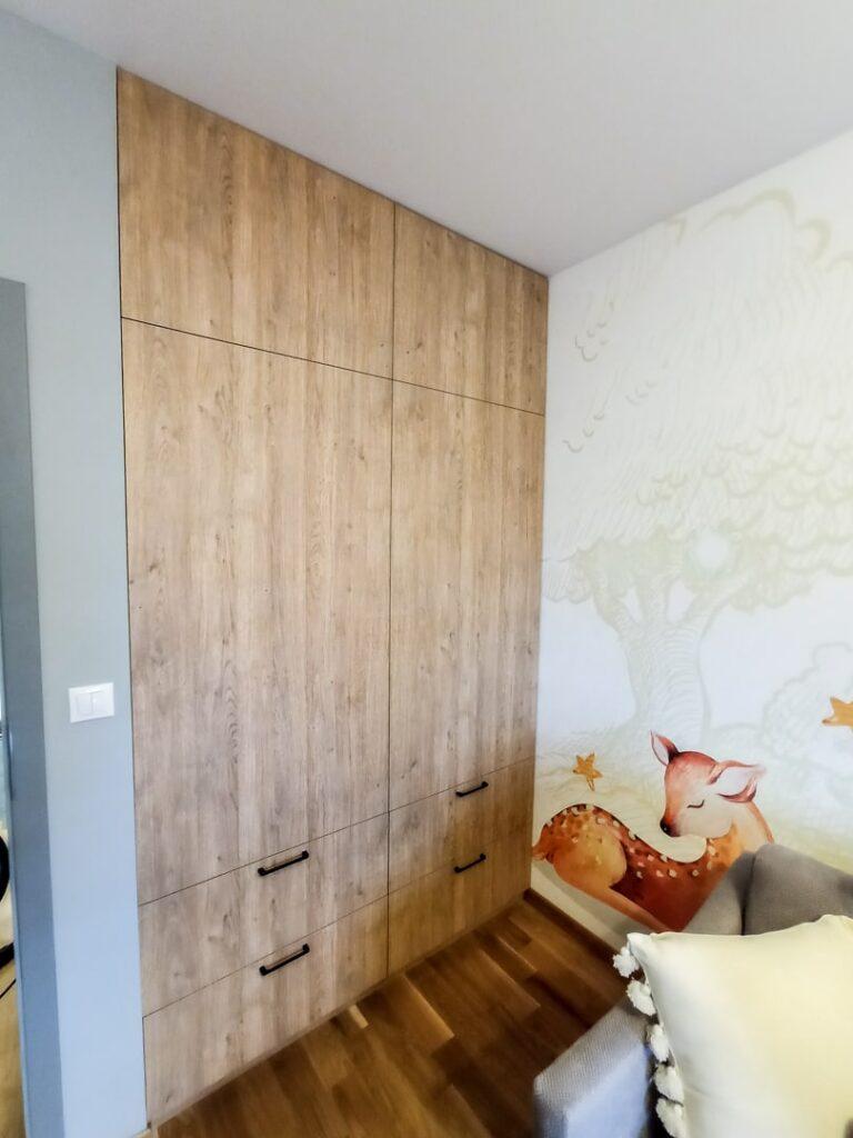 Zamknięta szafa drewnopodobna z szufladami w sypialni
