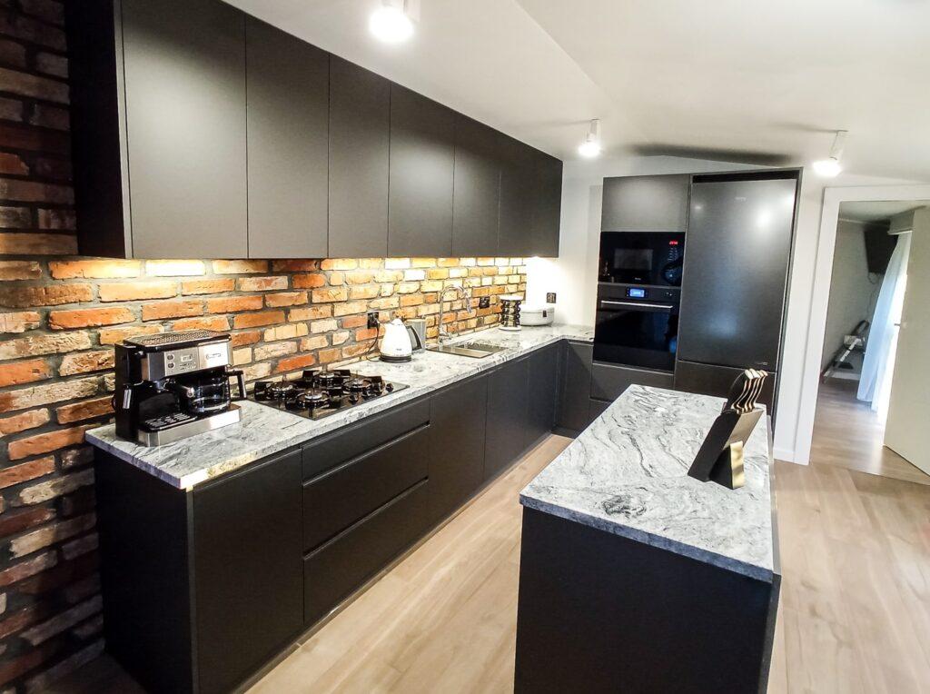 Czarna matowa kuchnia w stylu loftowym z blatem z konglomeratu