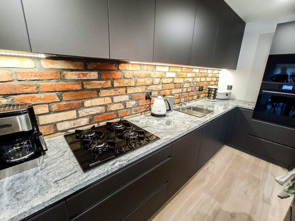 Blat konglomeratowy i kuchenka gazowa w kuchni loftowej