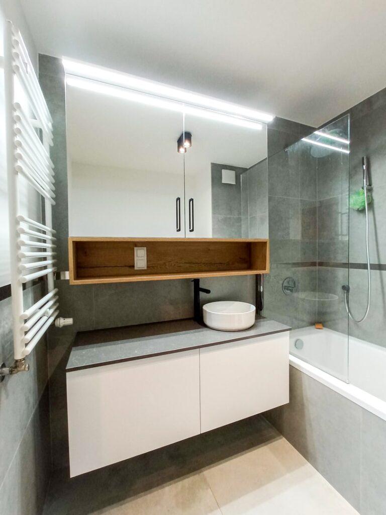 Biała szafka pod umywalkę z 2 szufladami oraz szafka lustrzana z półką w łazience