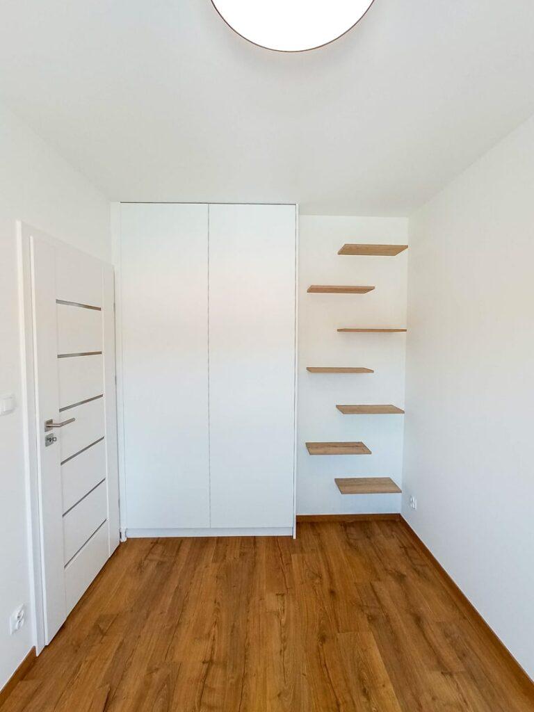 Biała szafa pod sufit z półkami drewnianymi na ścianie