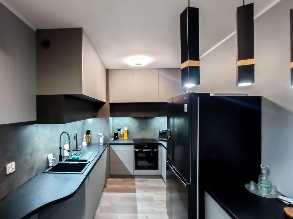 Czarno szara kuchnia na wymiar z fartuchem i sprzętem AGD