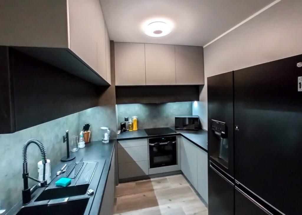 Czarna lodówka wolnostojąca w kuchni z płytą zablatową