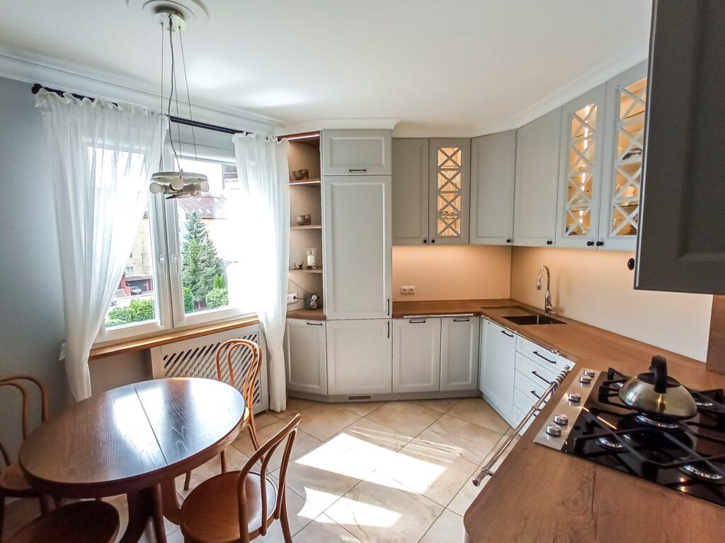 Biała kuchnia na wymiar z drewnianym blatem i witrynami ze szprosami