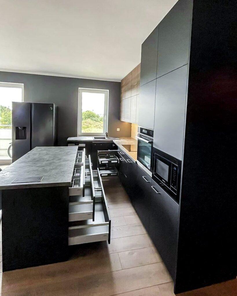 czarna kuchnia z wyspą oraz dużą ilością szuflad wewnętrznych