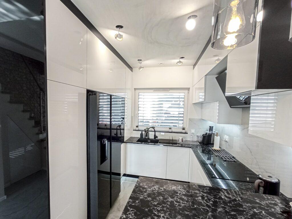 biało-czarna kuchnia z akrylowymi frontami oraz kamiennym blatem