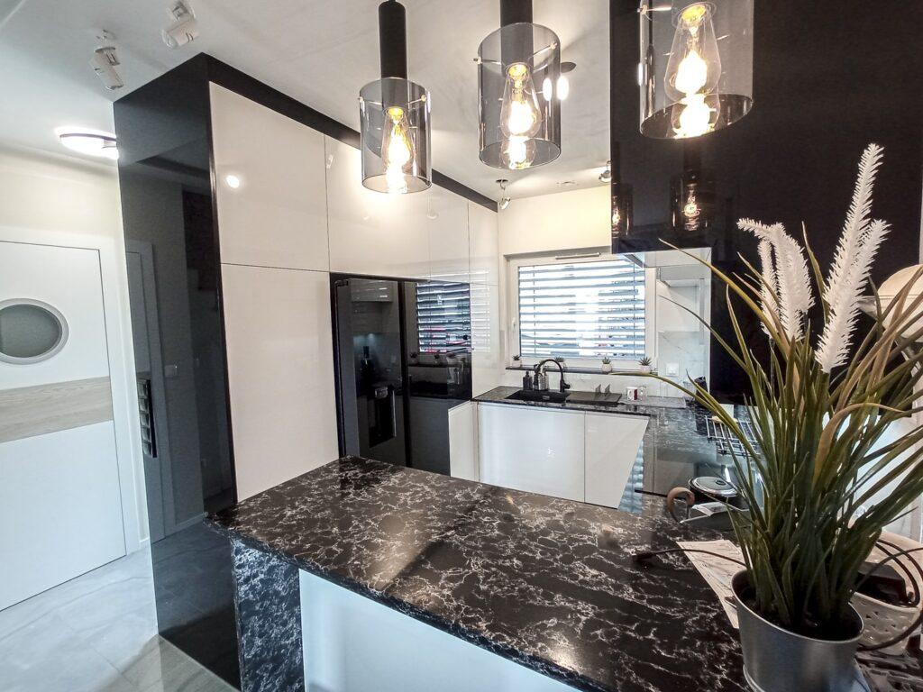 biało-czarna kuchnia na wymiar z akrylowymi frontami oraz kamiennym blatem