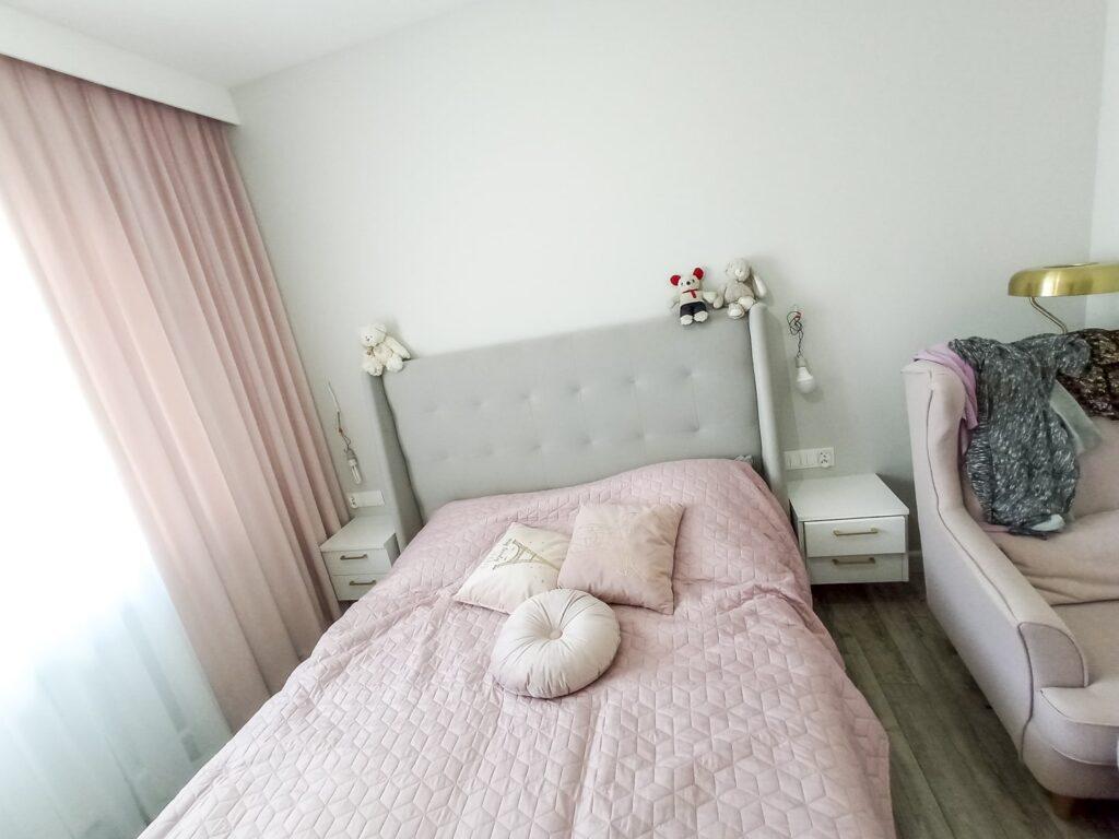 białe szafki nocne ze złotymi uchwytami obok łóżka z panelem tapicerowanym w sypialni