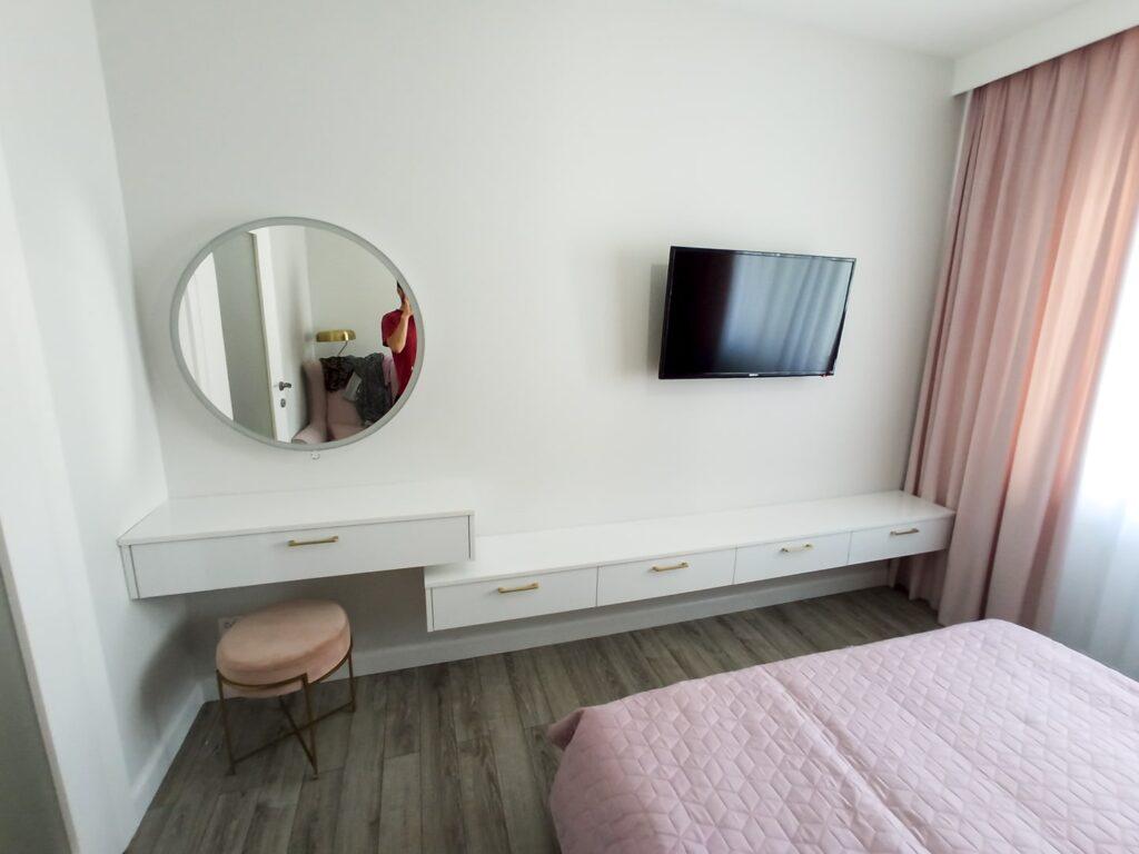 białe podłużne szafki na ścianie, wraz z lustrem i stołkiem